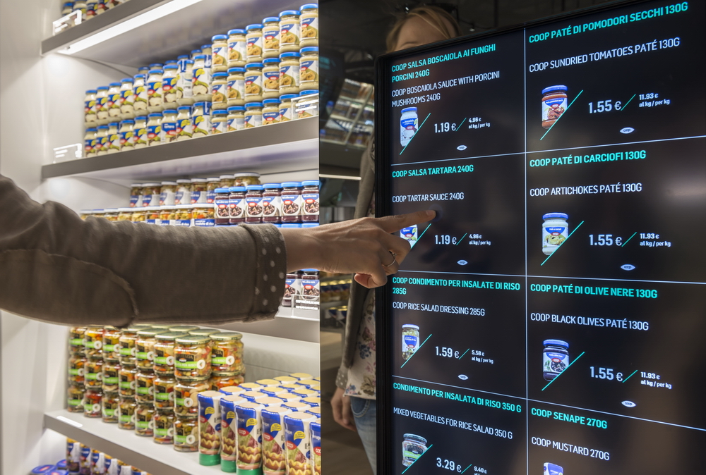 A futuristic representation of grocery shopping, featuring a person selecting groceries through a touch-screen grid.